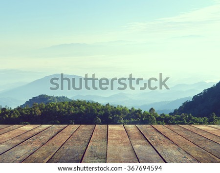 Wood terrace with perspective view on mountain hills and mist. Vintage style.