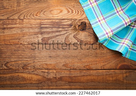 Wood texture background. Wooden table covered with tablecloth cloth checkered plaid red. View from top. Empty tablecloth for product montage for recording menu, recipe. Free space for your text