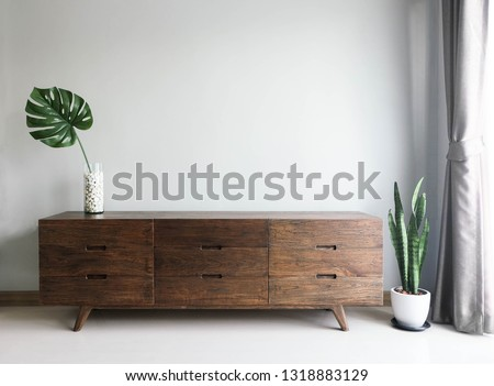 Photo of Wood TV cabinet interior wall Mockup with small plant tropical style in living room place with free space in center of picture for present the product. image