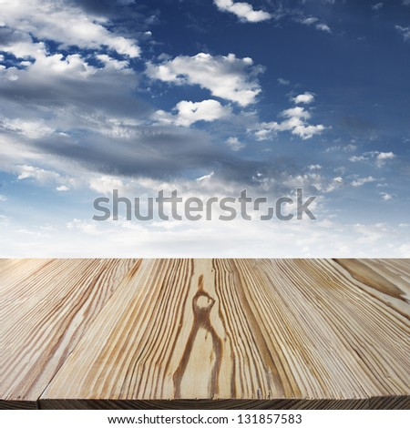 Wood walkway with blue sky with clouds in the background