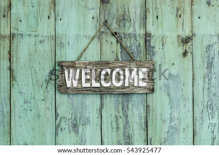 Wood welcome sign hanging by rope on antique rustic shabby mint green wooden background; weathered sign with painted copy space