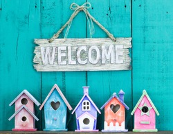 Wood welcome sign hanging over row of colorful spring birdhouses with antique teal blue rustic wooden background; purple, orange, pink, green
