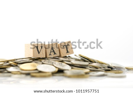 Wood word VAT is placed on a pile of coins.using as background business concept and finance concept with copy spaces for your text or design.