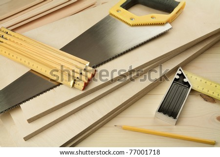 Wood working tools on a wooden boards background. Including saw, ruler, pencil, square.