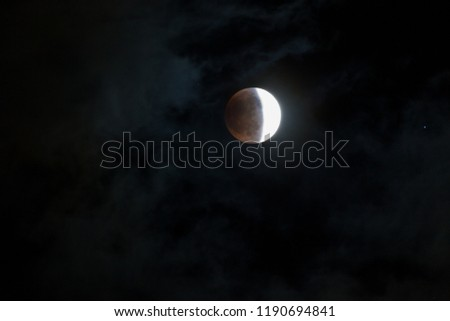 WOODBURN, OREGON - April 14, 2014:  The blood moon at the middle stage of a total lunar ellipse with a  night sky and thin cloud background in Woodburn, OR on April 14, 2014. #1190694841
