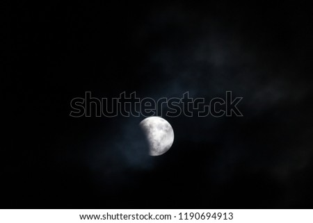 WOODBURN, OREGON - April 14, 2014:  The blood moon at the very beginning stages of a total lunar ellipse with a  night sky and thin cloud background in Woodburn, OR on April 14, 2014. #1190694913
