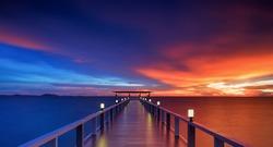 Wooded bridge in the beach island portalong the sunrise time.