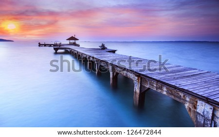 Wooded bridge in the port between sunrise.