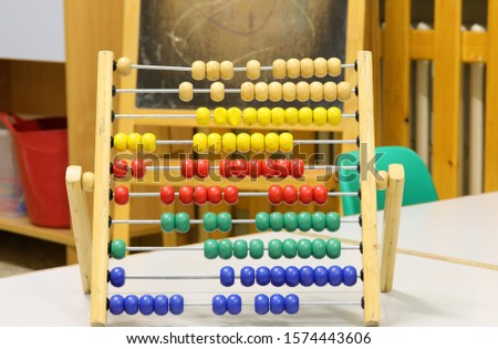 Wooden Abacus with many small beads on the table in the classroom of primary school