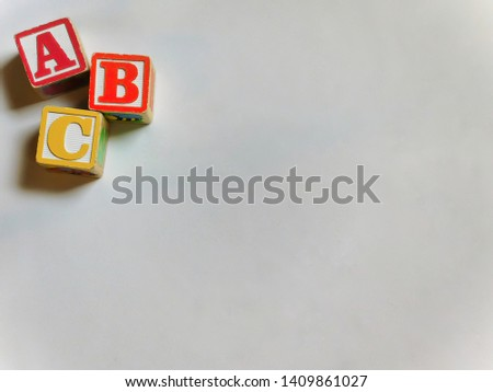 Wooden ABC blocks on corner on white backdrop, with copy space, lit with natural light