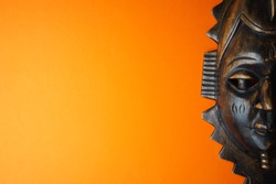 Wooden african mask on orange background