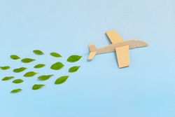 Wooden airplane model emitting fresh green leaves on blue background. Sustainable travel; clean and green energy; and biofuel for aviation industry concept.