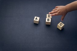 Wooden alphabet cube with words ABCD closeup and children hands on black background. Selective focus and education concept