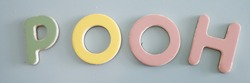 Wooden alphabet 3D magnets in pastel colors, pink, green, yellow, and blue. Alphabetized, spelled