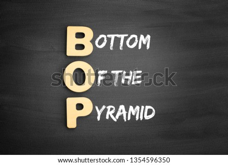 Wooden alphabets building the word BOP - Bottom of the Pyramid acronym on blackboard