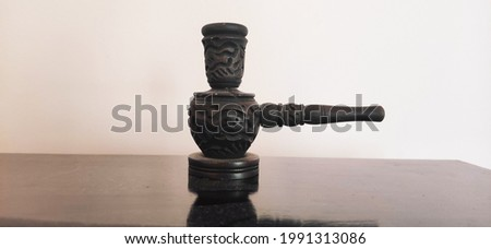 Wooden and artisan smoke pipe on table. Inlaid wooden native pipe, close up and isolated side view Stok fotoğraf ©