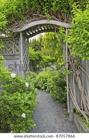 Wooden arbor and fence in a perennial garden or park like setting.