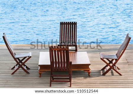 Wooden area with chairs and table on calm blue water