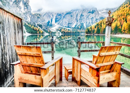 Wooden armchairs at the bank of famous and very popular travel destination lake Braies - lago di Braies, South Tyrol in Italy, Europe. Fall season, yellow leaves trees at background. Autumn time.