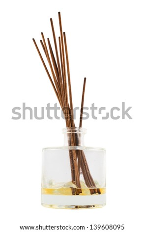 Wooden aroma sticks in a glass flask filled with flavor liquid substance isolated over white background, side view