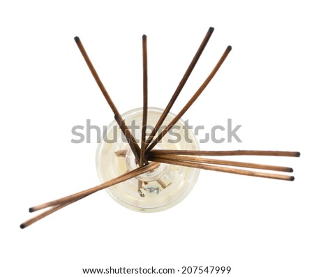 Wooden aroma sticks in a glass flask filled with flavor liquid substance isolated over white background, top view
