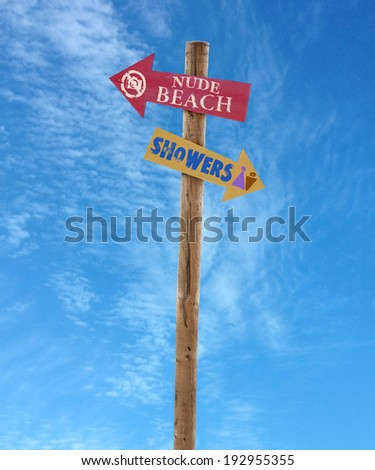 wooden arrow direction signs post to the nude beach and showers against a blue sky