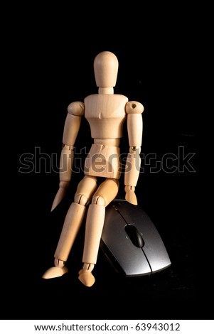Wooden Art Doll Sitting on Computer Mouse