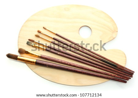 wooden art palette and brushes isolated on white