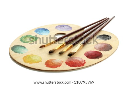 wooden art palette with paint and brushes isolated on white