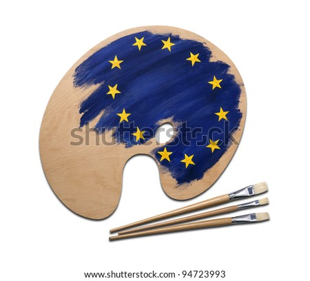 wooden artists palette loaded with european flag paints and brush, isolated on a white background with clipping path.
