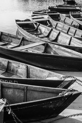 Wooden authentic old boats on the river bank. Life in the village of ordinary people. Transport and fishing vehicle. Black and white photo.