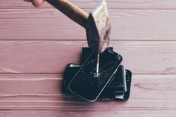 wooden background. man hammering a nail into a smartphone. they are damaged. close-up