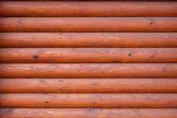 Wooden background of red-brown logs. Wall with beautiful pattern and wood structure.