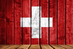 Wooden background with a flag of Switzerland.