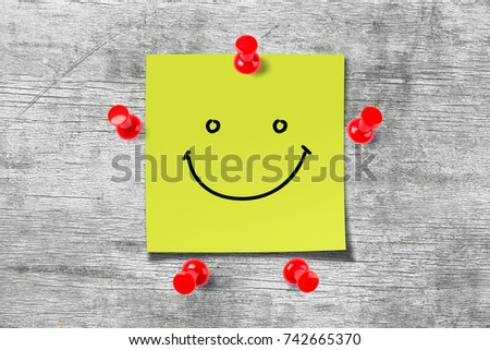 Wooden background with a smile face sticky note. #742665370