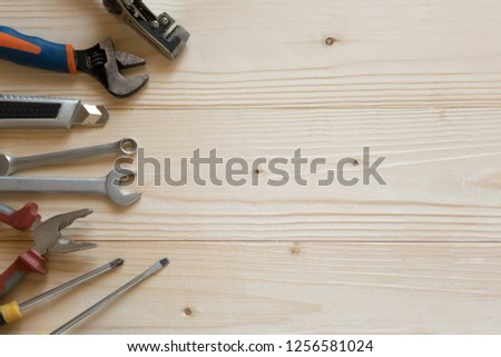 Wooden background with a tools. Banner for a hardware store and a building company. Screwdrivers, pliers, electrical tape. #1256581024
