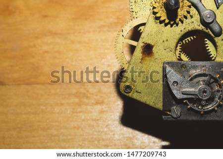 Wooden background with detail of a clock mechanism. gears of a mechanical watch