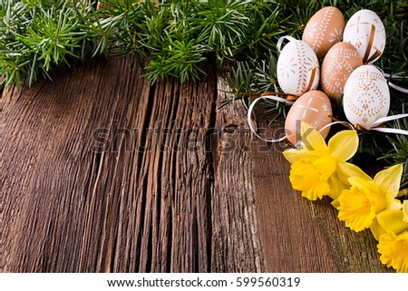 Wooden background with Easter eggs and daffodils. #599560319