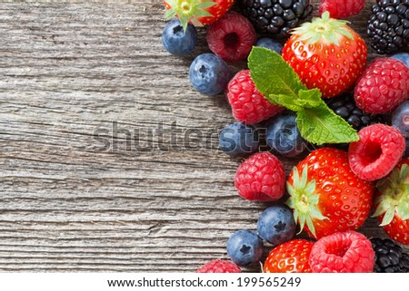wooden background with fresh berries and mint, top view #199565249