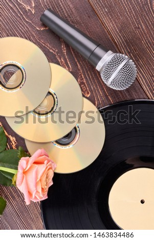 Wooden background with musical objects. Vinyl record, blank cd or dvd discs, microphone and rose. Music still life.