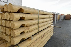 Wooden balk, timber, beam and building material stacked at construction site. Wooden planks, lining, boards for construction works in the sawmill.