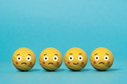 Wooden balls with emoticons of sadness and happiness. Concept of mood change. Blue background