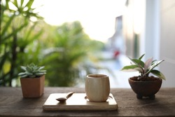 Wooden bamboo cup and plate and wooden spoon with cactus plant pot on table