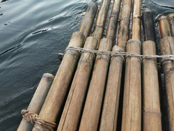 Wooden bamboo raft floating,Bamboo rafting stacked which is binding with rope line. Selective focus on the rope surface.