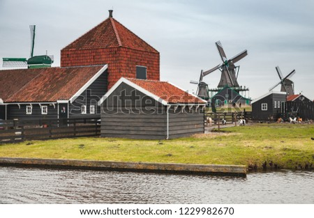 Wooden barns and windmills on Zaan river coast, Zaanse Schans town, popular tourist attractions of the Netherlands. Suburb of Amsterdam