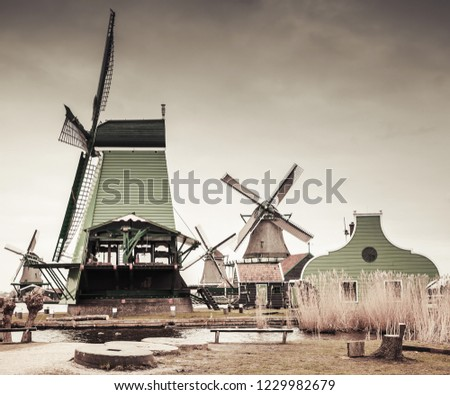 Wooden barns and windmills on Zaan river coast, Zaanse Schans town, popular tourist attractions of the Netherlands. Suburb of Amsterdam. Retro stylized photo with gradient tonal correction filter