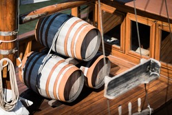 Wooden barrels on the deck of a small sailing ship