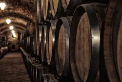 Wooden barrels with whiskey in dark cellar