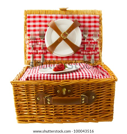 Wooden basket for picnic with plates and a strawberry isolated over white