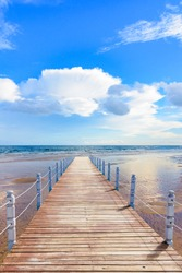 wooden batten bridge juts out into the expanse of the sea